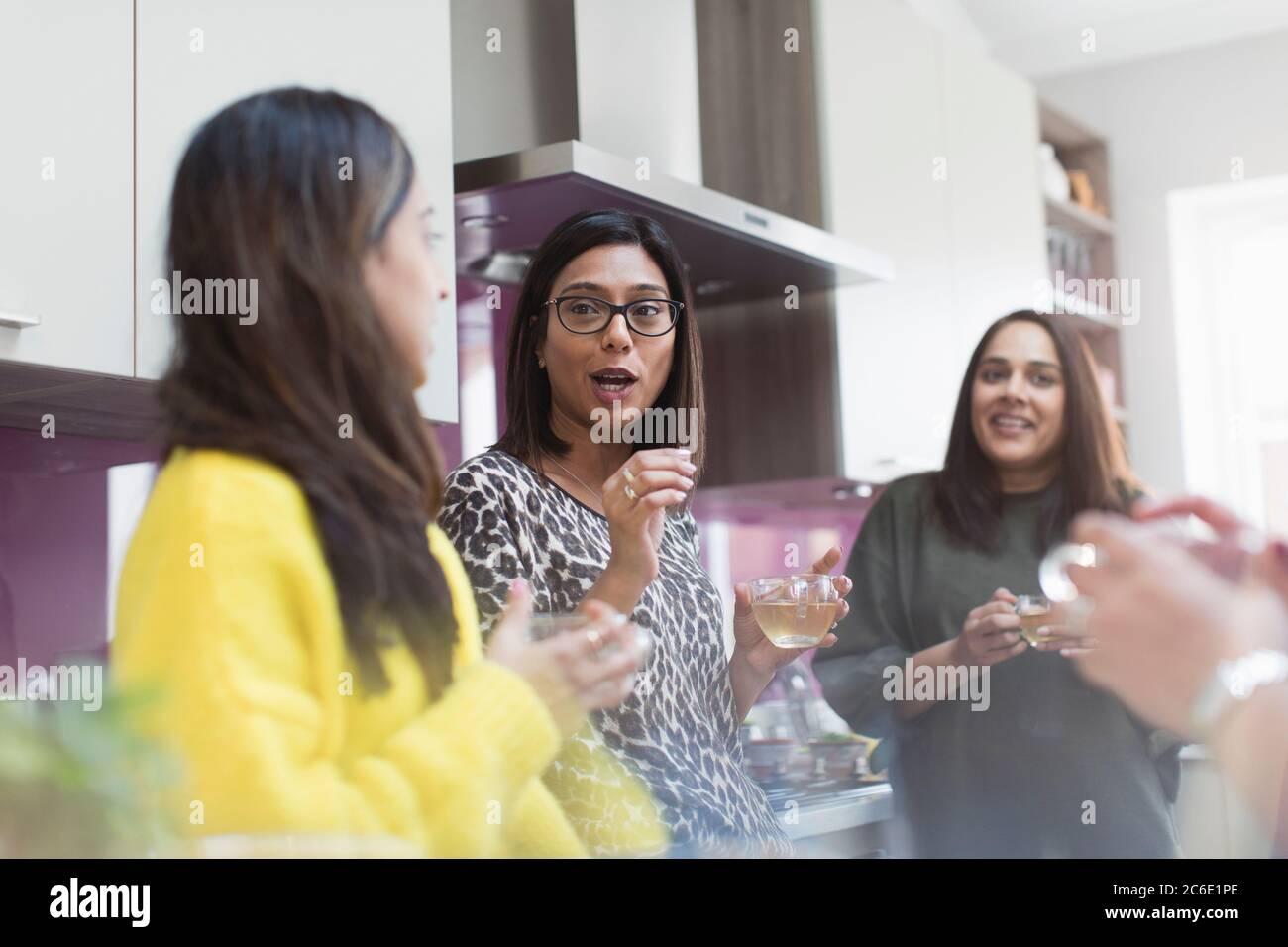 Women talking and drinking tea in kitchen Stock Photo