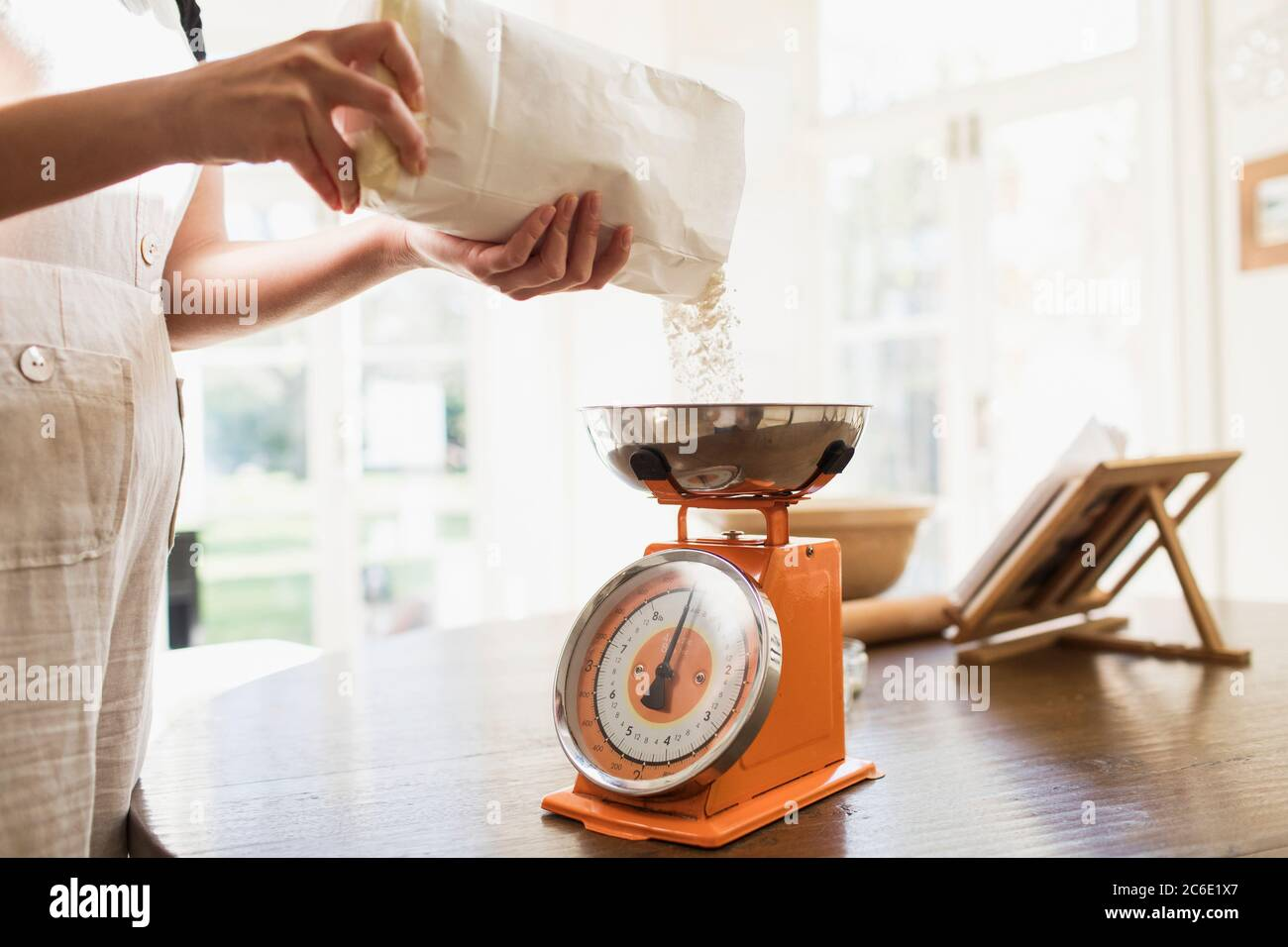 Woman measuring flour for baking in kitchen Stock Photo