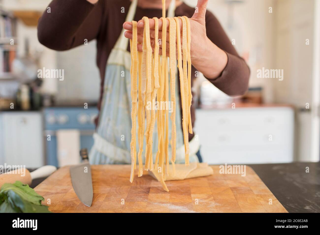 Close up woman making fresh homemade pasta in kitchen Stock Photo