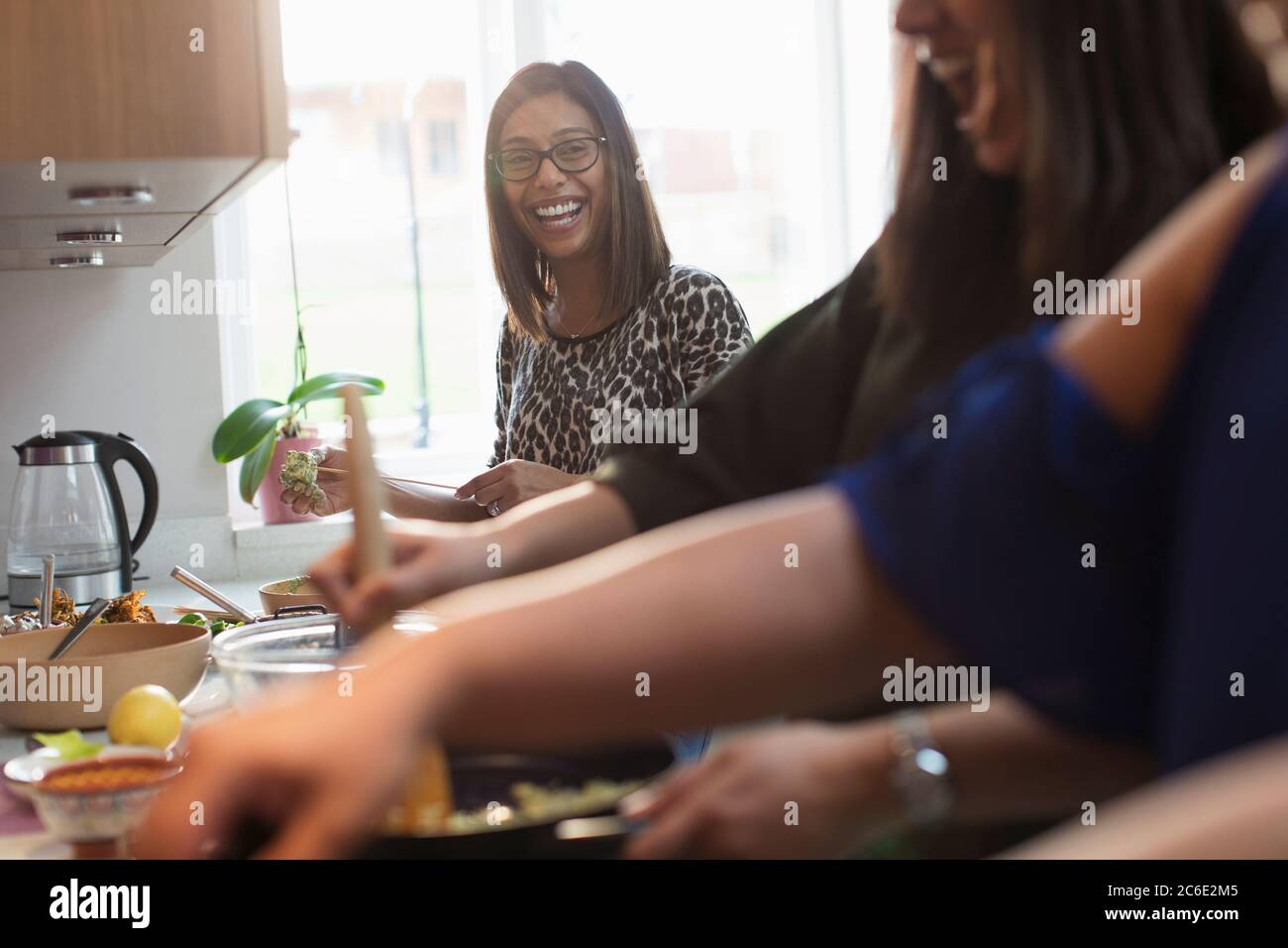 Happy Indian women cooking food in kitchen Stock Photo