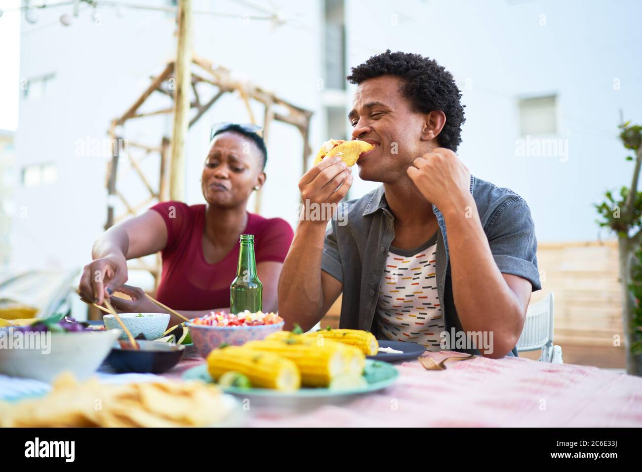 Young man eating taco lunch at patio table Stock Photo