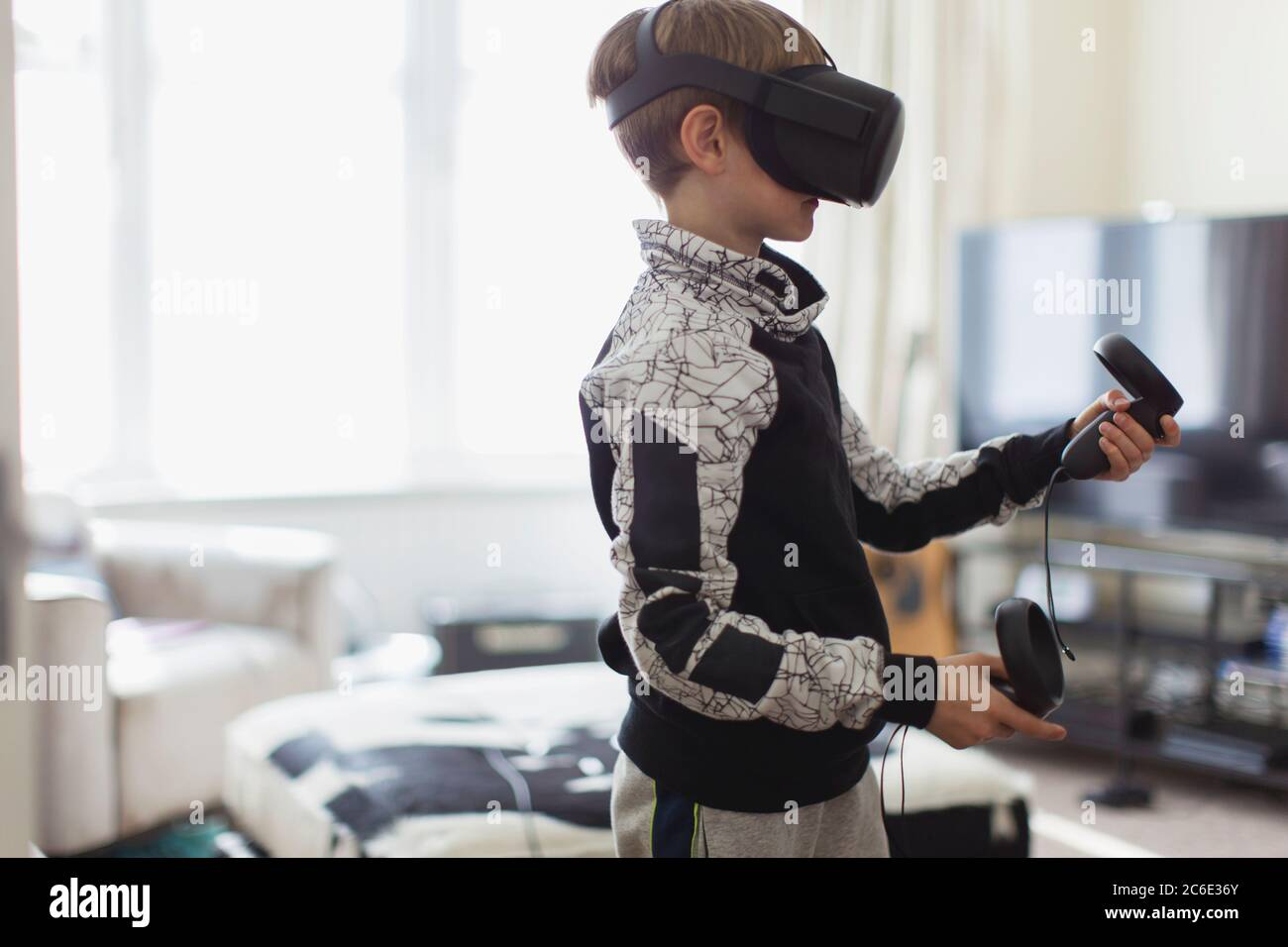 Boy playing video game with VRS goggles in living room Stock Photo