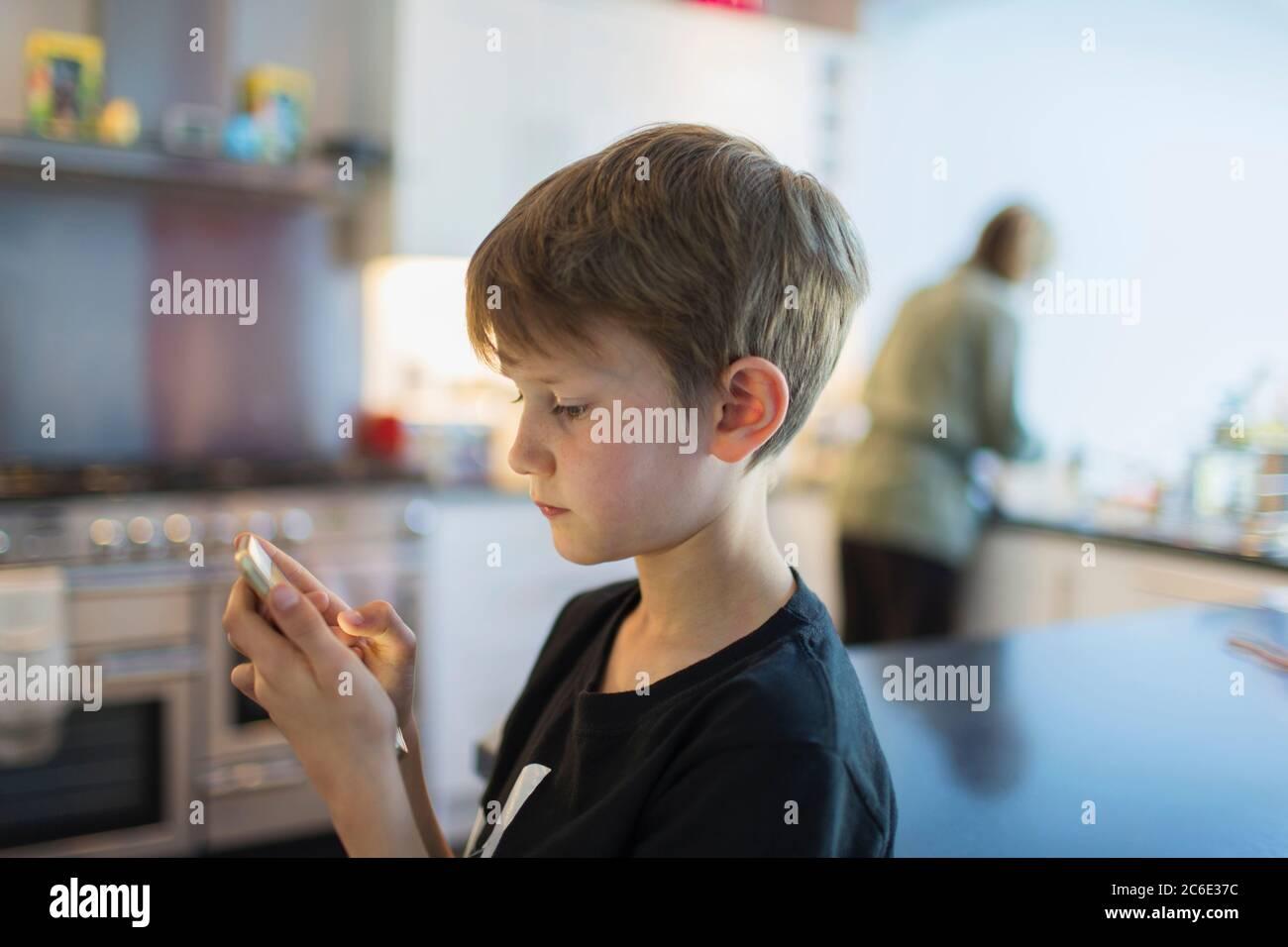 Boy using smart phone in kitchen Stock Photo