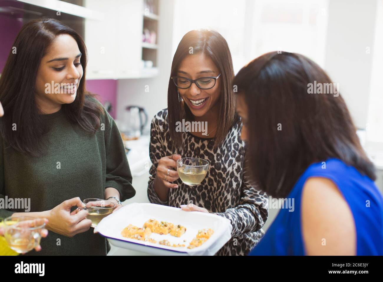 Happy Indian women with tea and food in kitchen Stock Photo