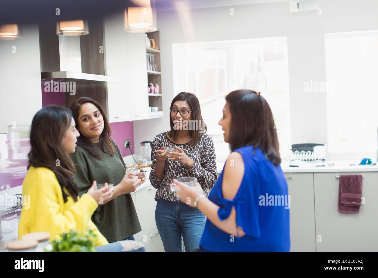 Indian women talking and drinking tea in kitchen Stock Photo