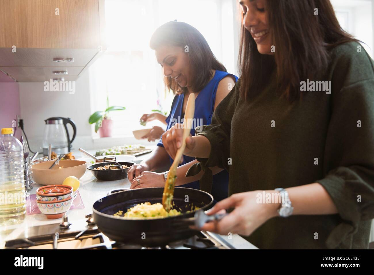 Indian women cooking food in kitchen Stock Photo