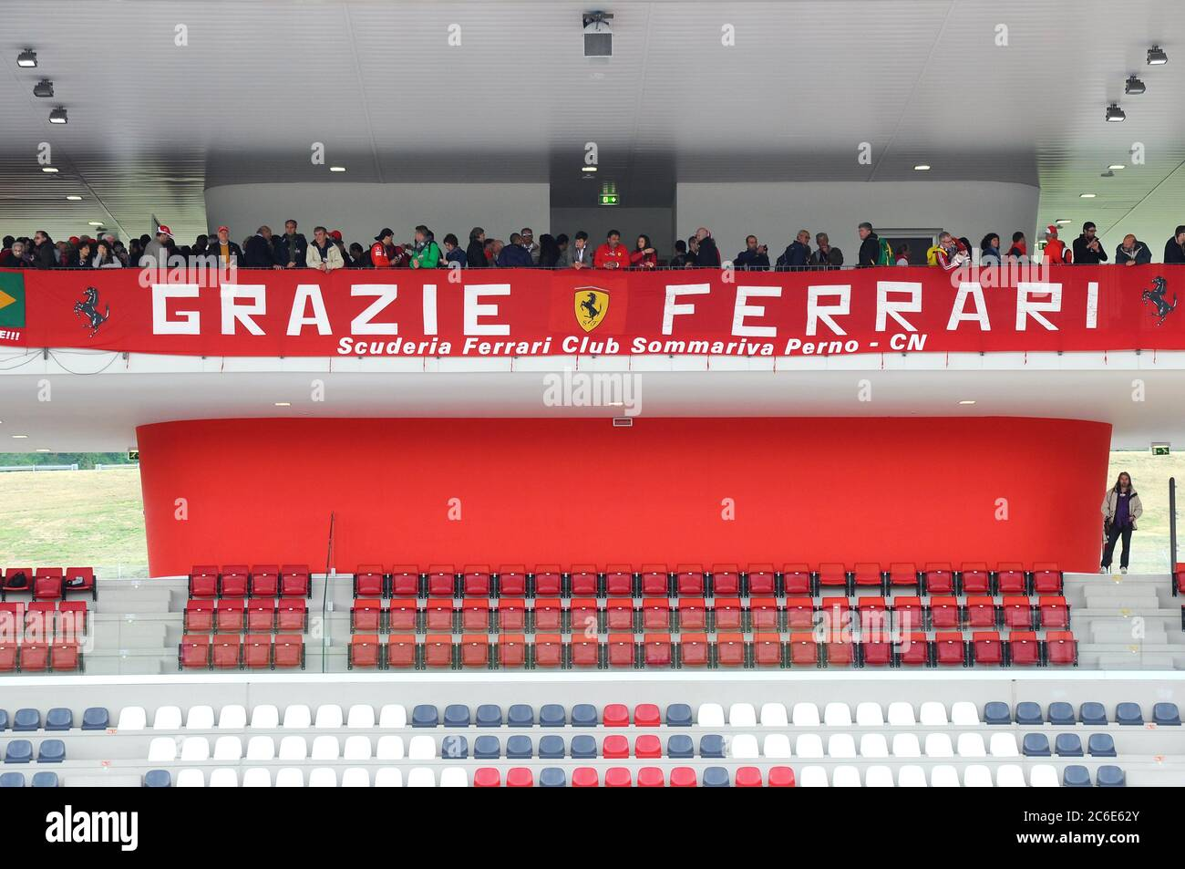 """MUGELLO, ITALY - MAY 2012: fans and banner with """"thank you Ferrari"""" on the central grandstand of the Mugello international Circuit. Stock Photo"""