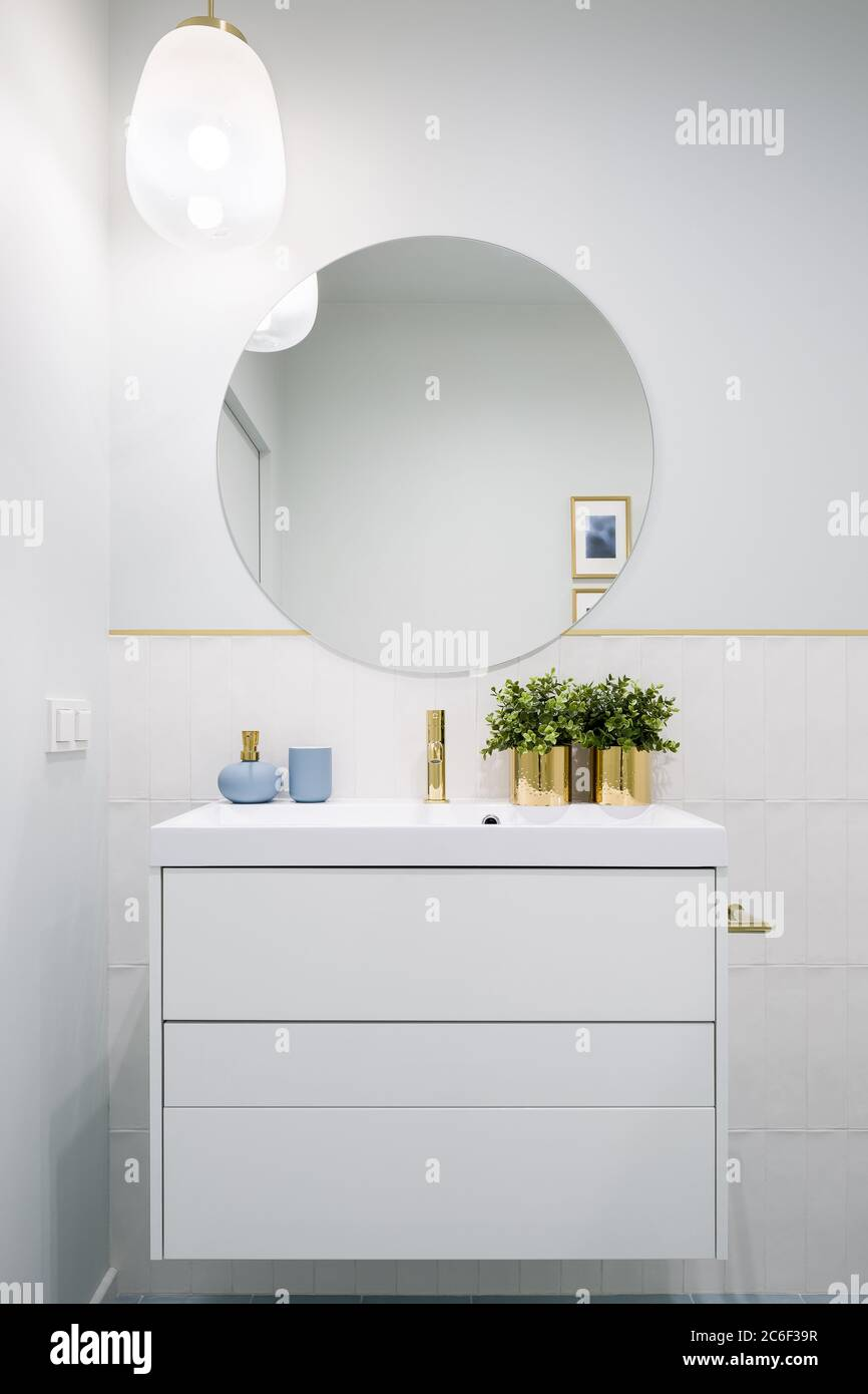 Bathroom With Round Mirror And White Cabinet With Drawers Stock Photo Alamy