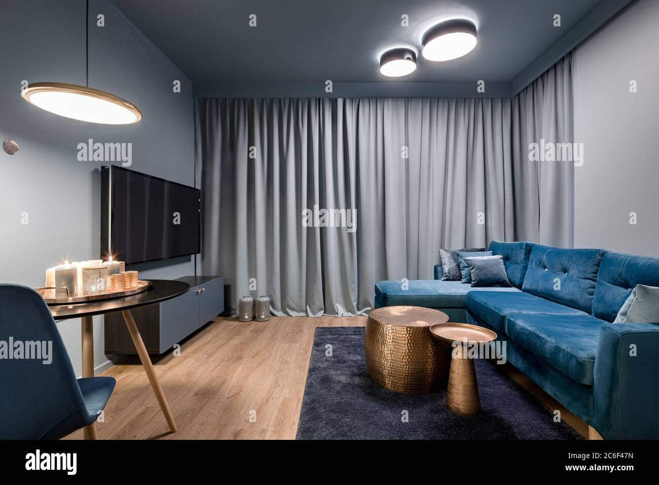 Picture of: Elegant Living Room With Big Blue Sofa Two Copper Coffee Tables And Tv Screen Stock Photo Alamy