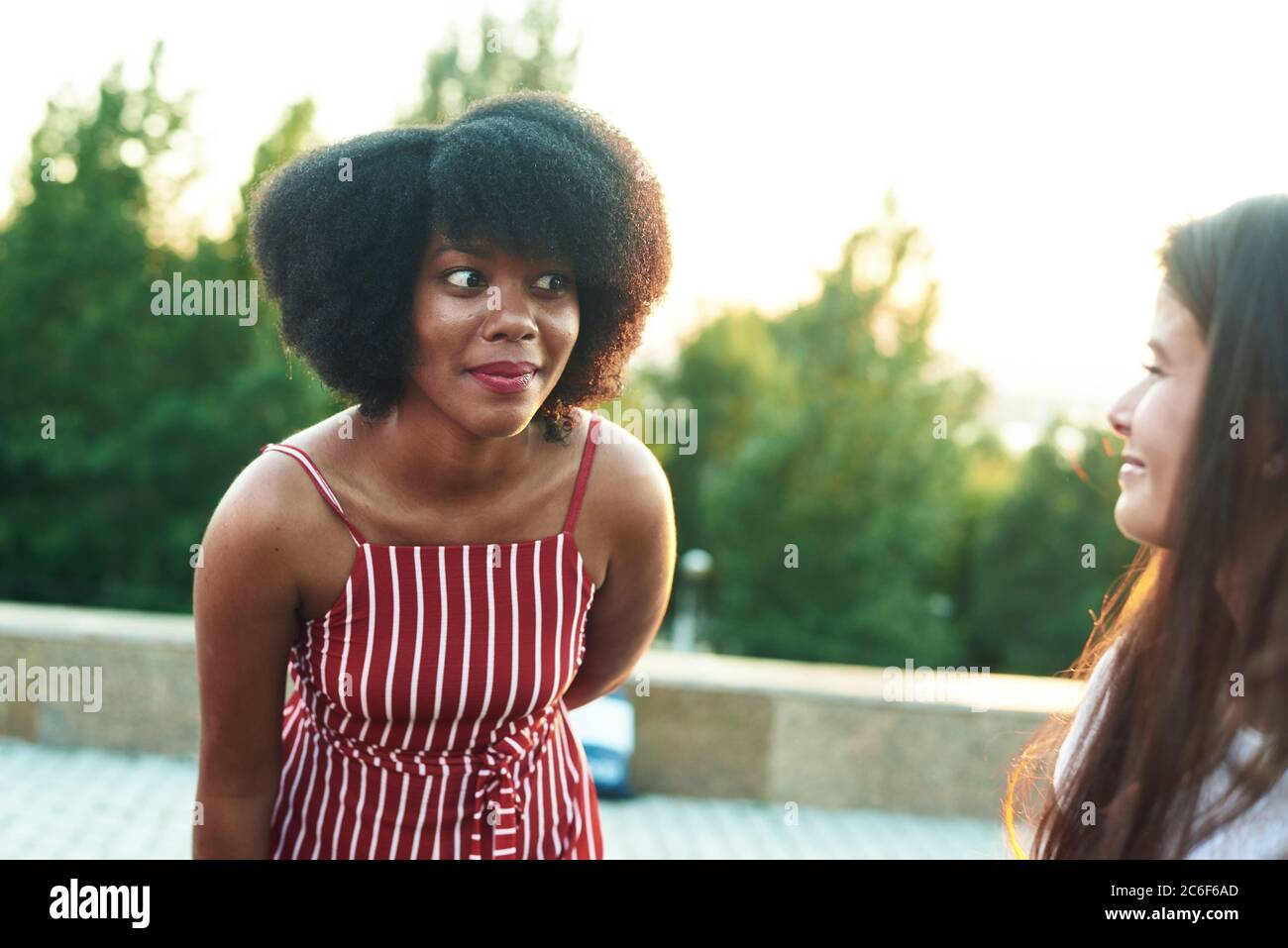 Astonished black girl listens to gossip from her friend. Stock Photo