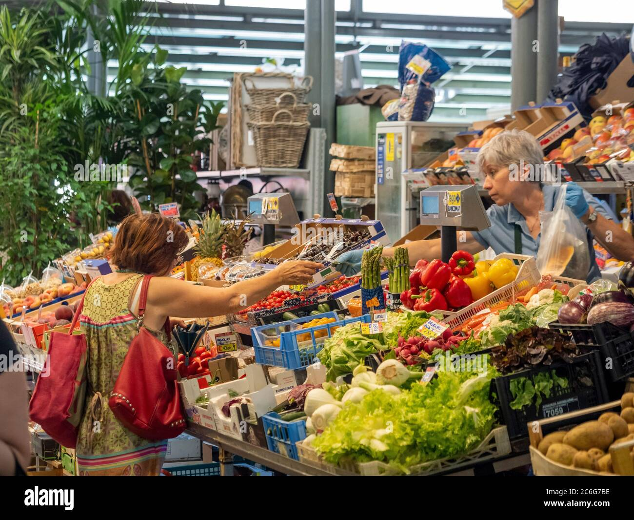 Customer paying for her Fruit and Vegetables on a stall in Mercato Albinelli, Modena, Italy. Stock Photo