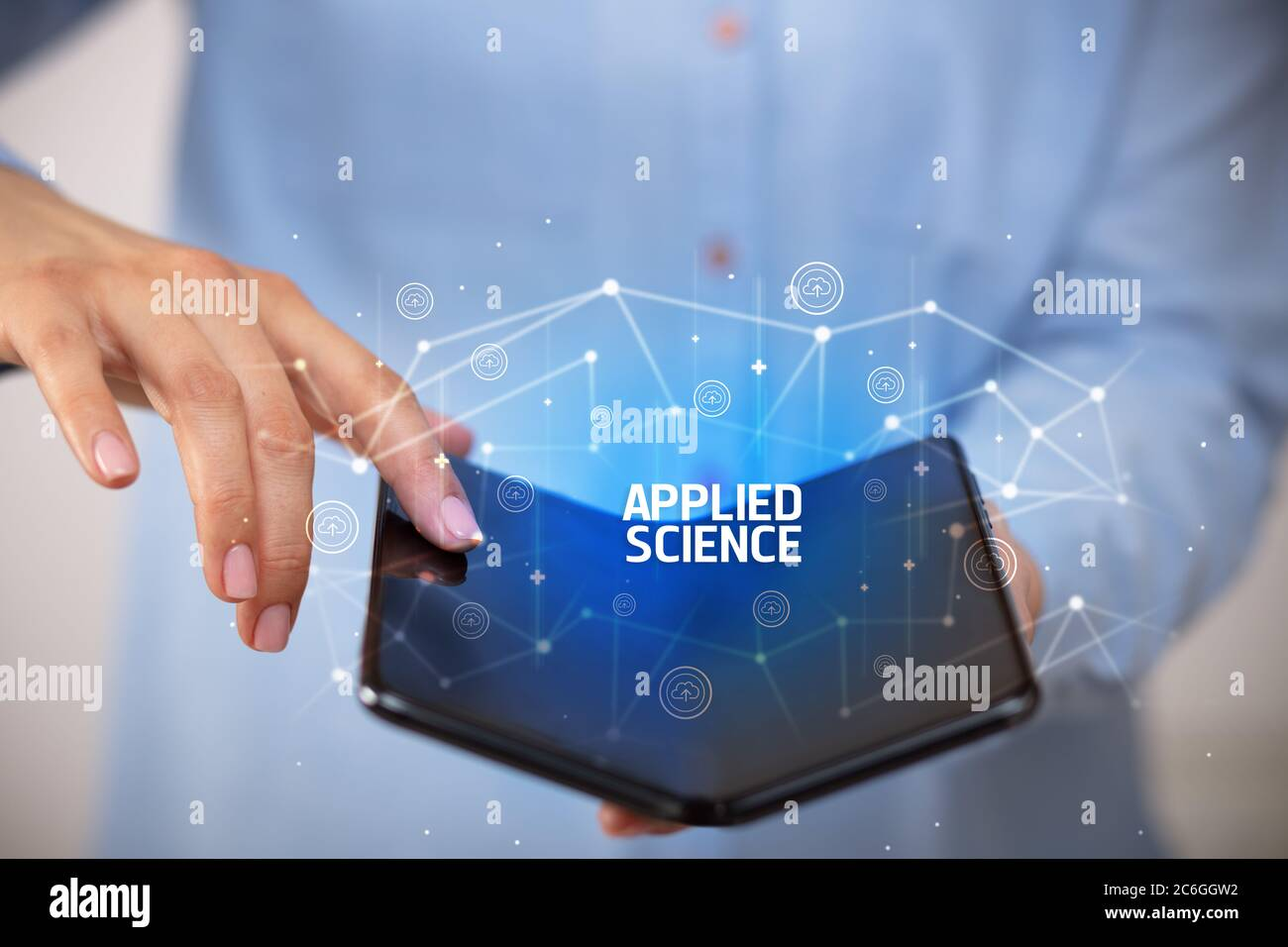 Businessman holding a foldable smartphone with APPLIED SCIENCE inscription, new technology concept Stock Photo