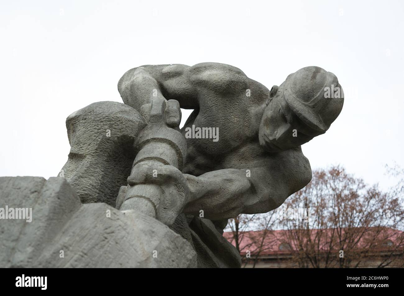 Historic statue made in socialist realism style. Realistic muscular mineworker is holding pneumatic drill. Glorification of manual work and mining and Stock Photo