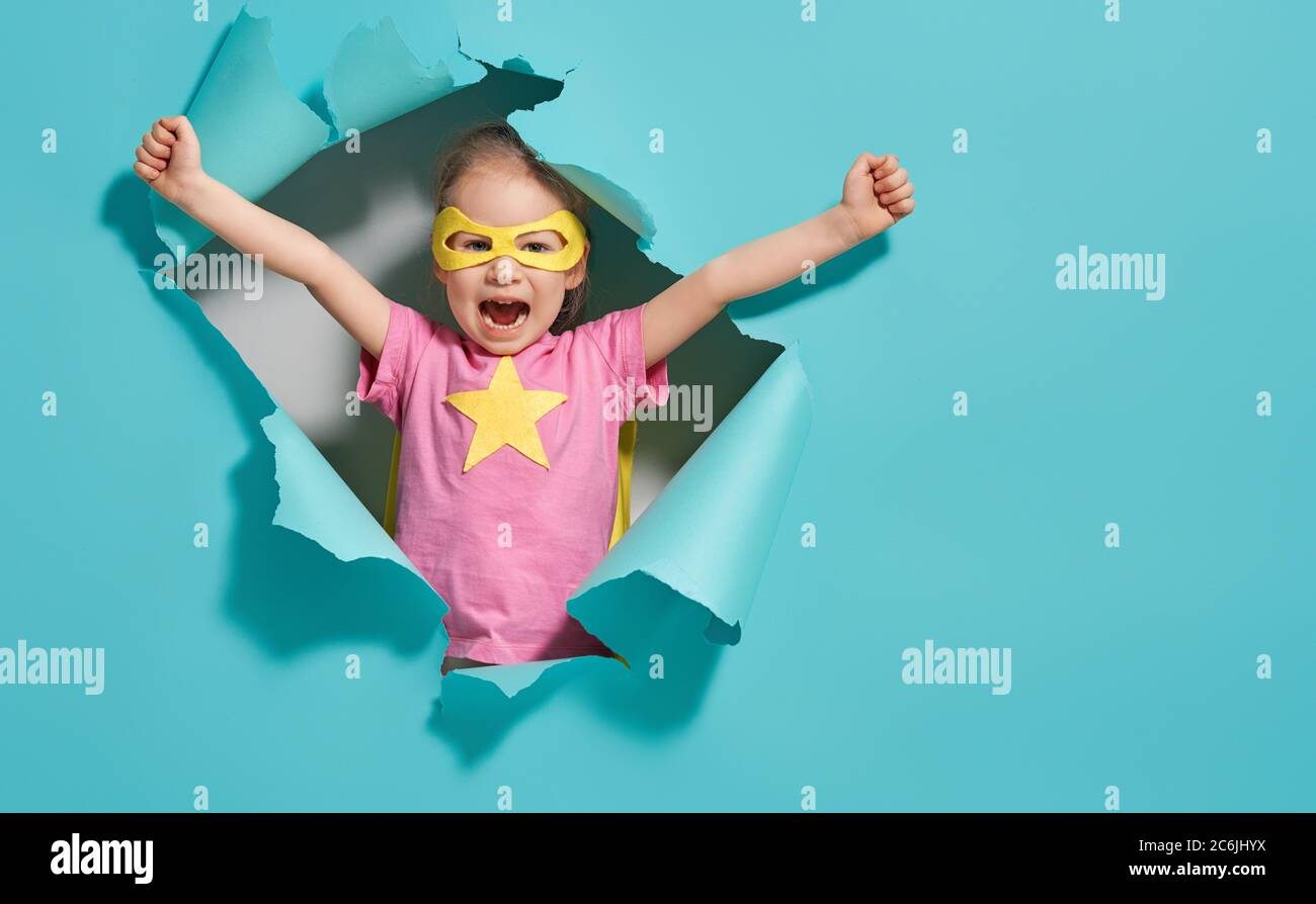 Little child playing superhero. Kid on the background of bright blue wall. Girl power concept. Yellow, pink and  turquoise colors. Stock Photo
