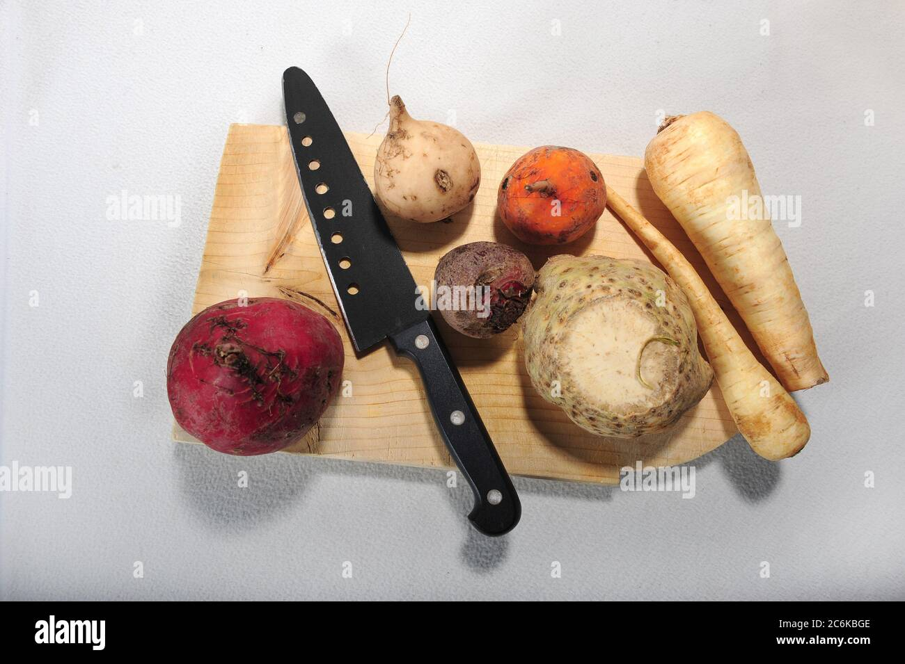 Different root vegetables on wooden cutting board along with knife. White background. High angle view. Stock Photo