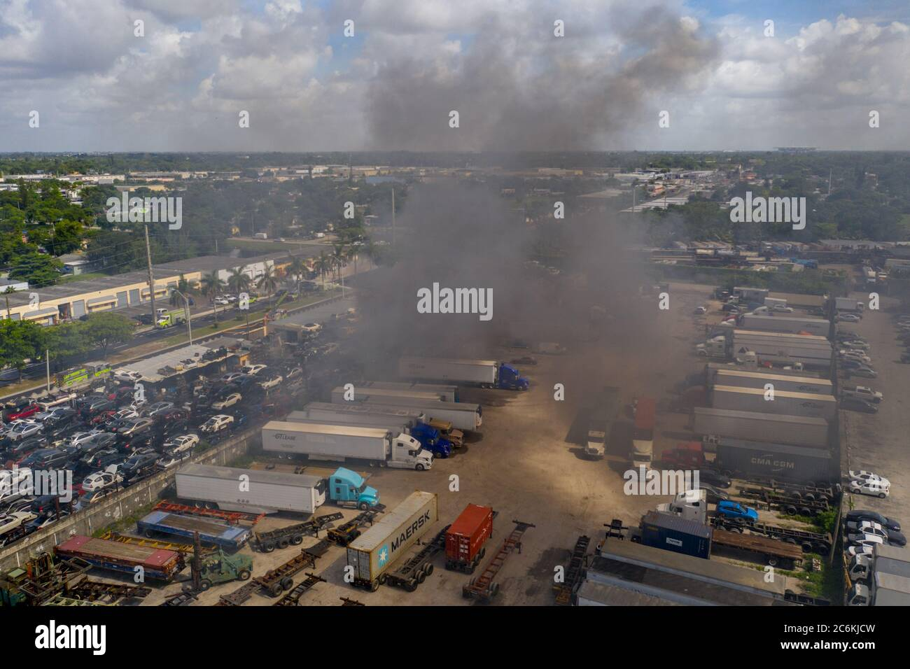 Aerial photo of a fire at a car junk yard firefighters water hosing flames extinguishing Stock Photo