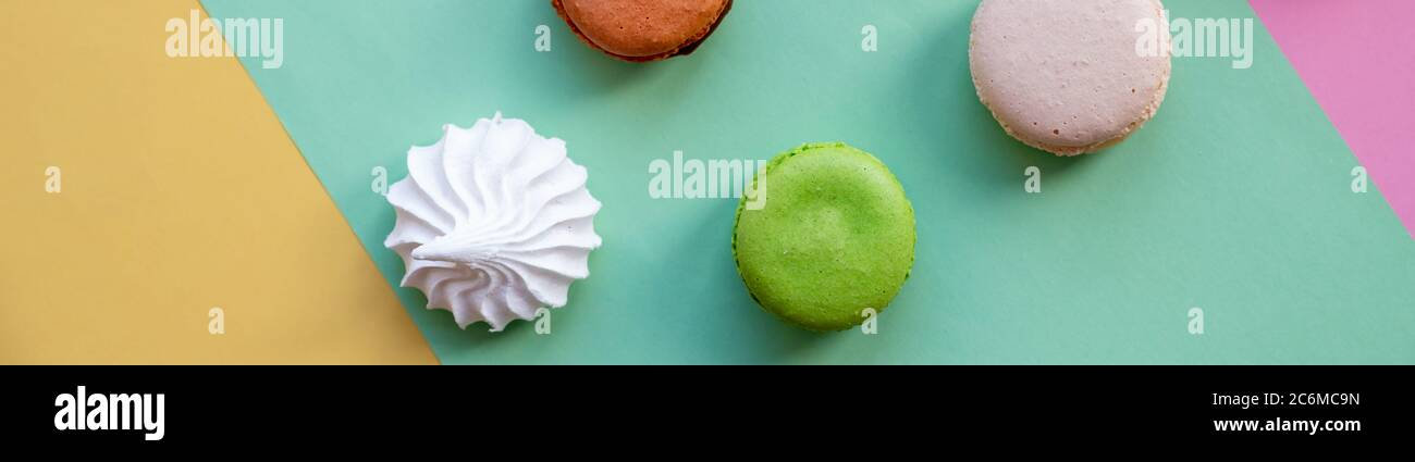 flat lay of colorful unstable french macaroon cookies like background, dessert concept.Pop Art Color style with meringue and bakery goodies on bright Stock Photo