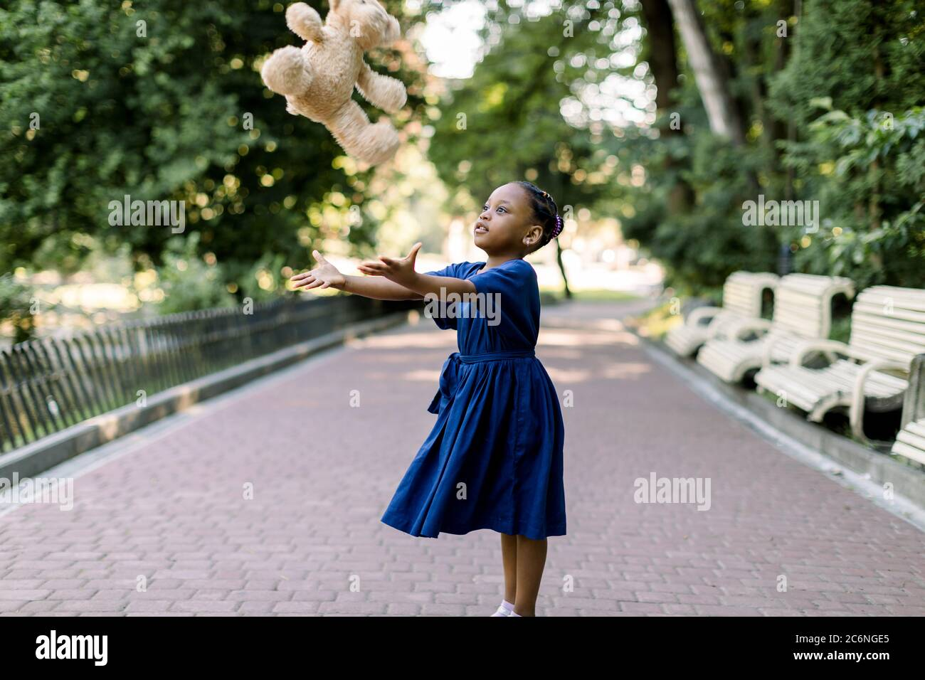 Portrait of happy little African girl child in green city park throwing up teddy bear toy, flying in the air. Smiling dark skinned kid girl in blue Stock Photo