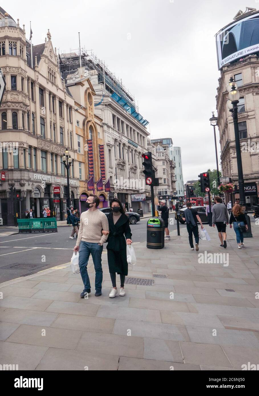 A man and woman with face coverings in Piccadilly Circus during the covid-19 pandemic. Stock Photo