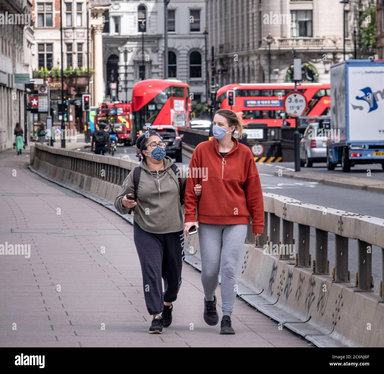 Two woman with face coverings in London during the covid-19 pandemic. Stock Photo