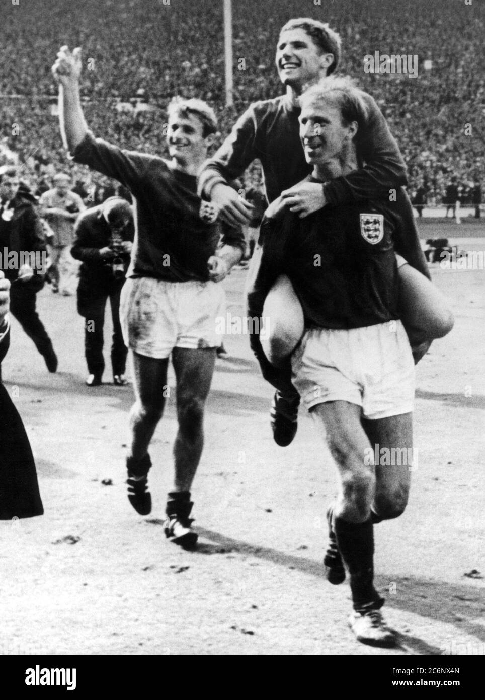 30 July 1966 Wembley Stadium, England. 1966 World Cup Final, Germany versus England.Jack Charlton carries Alan Ball as Roger Hunt (l) follows up the rear after beating Germany 4-2 after extra time is played. Stock Photo