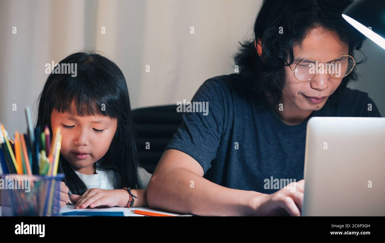 Father using laptop make overtime and daughter doing school homework on ofiice work table in home at night time Stock Photo