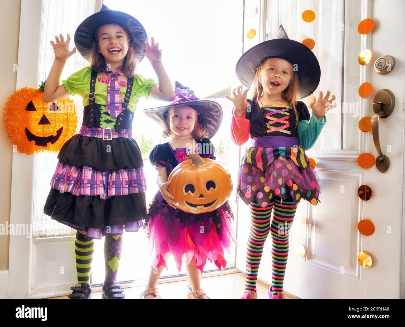 Happy Halloween Three Cute Little Laughing Girls In Witches Costumes Are Coming To The House For Sweets Stock Photo Alamy