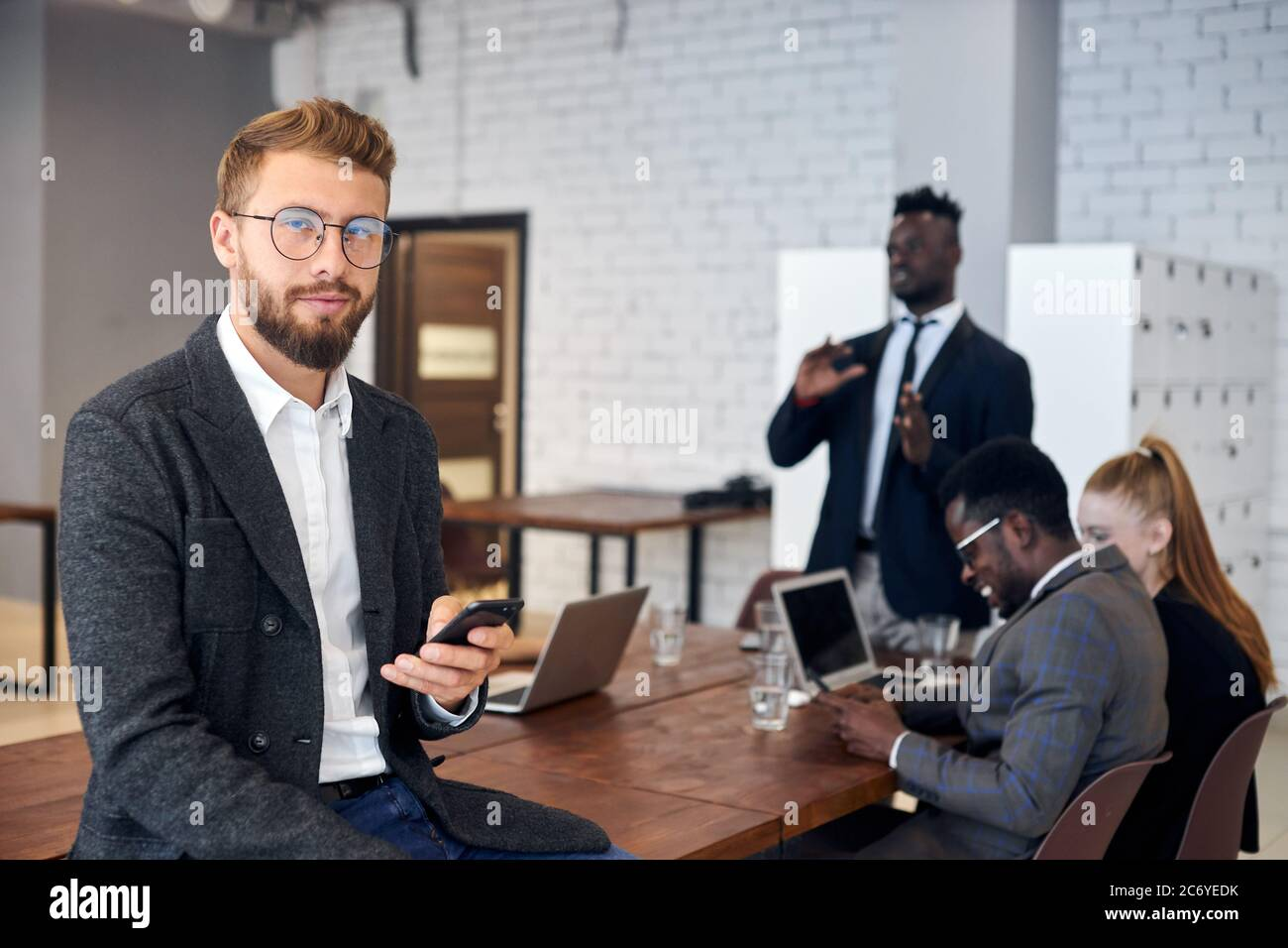 Handsome young man in tuxedo and eyeglasses using smartphone in workplace while his business colleagues having conversation in background Stock Photo