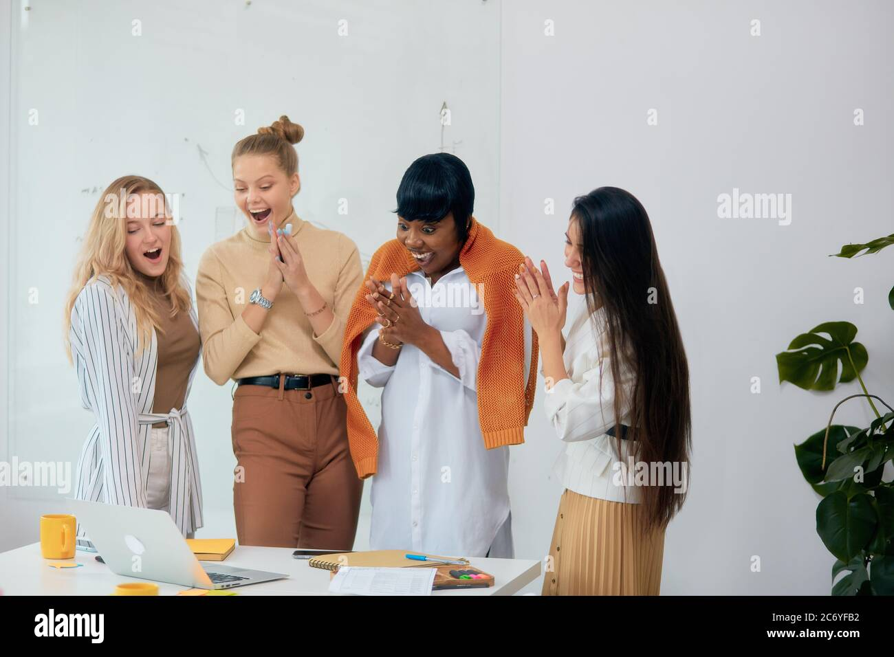 Surprised women in casual wear in office together, in shock with opened mouth. Celebrate their win in business project, good job of diverse female Stock Photo