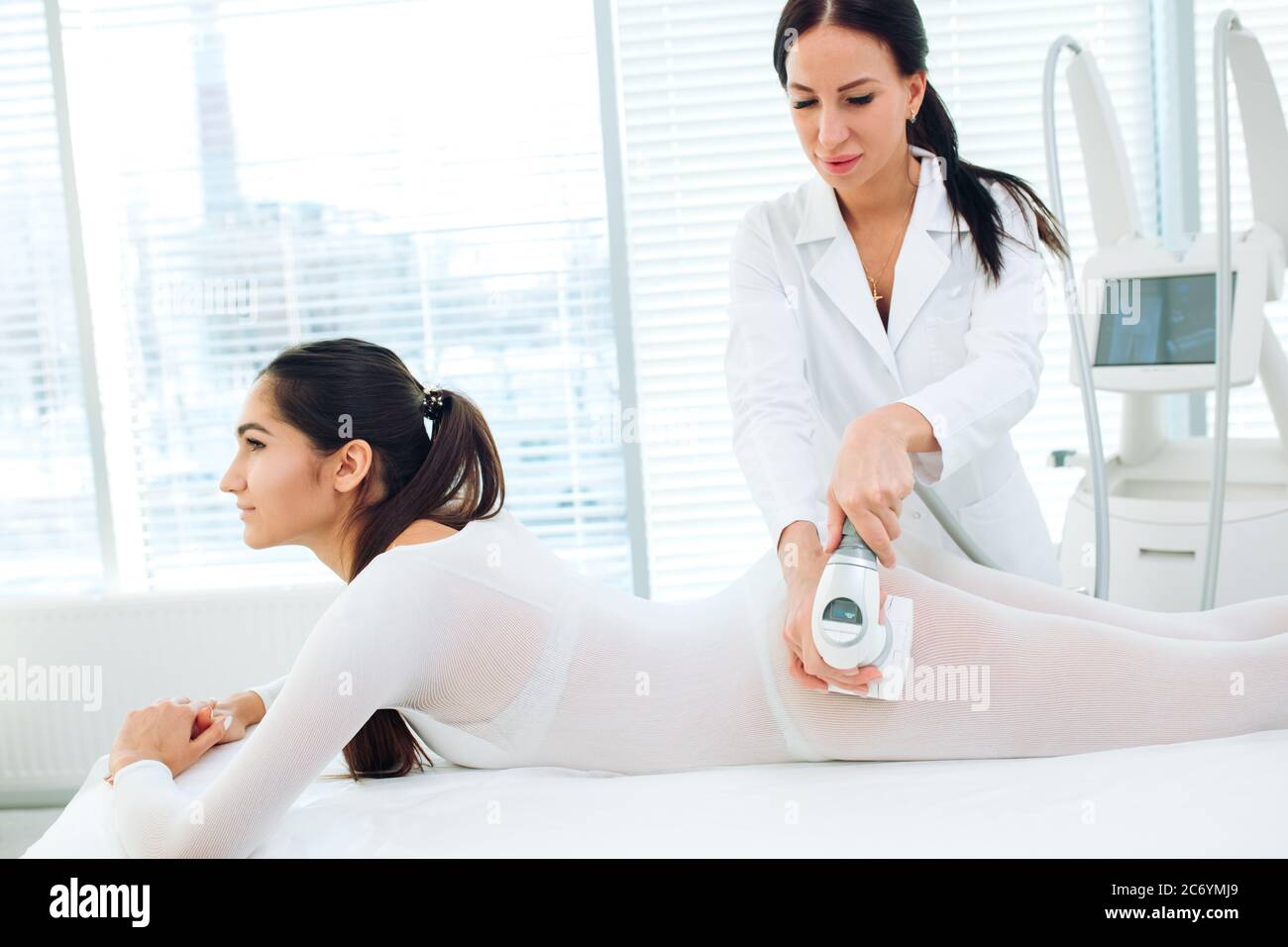 Close up shot of therapist beautician makes LPG massage treatment to young woman in white transparent suit, lying at beauty SPA clinic. Focus on hands Stock Photo