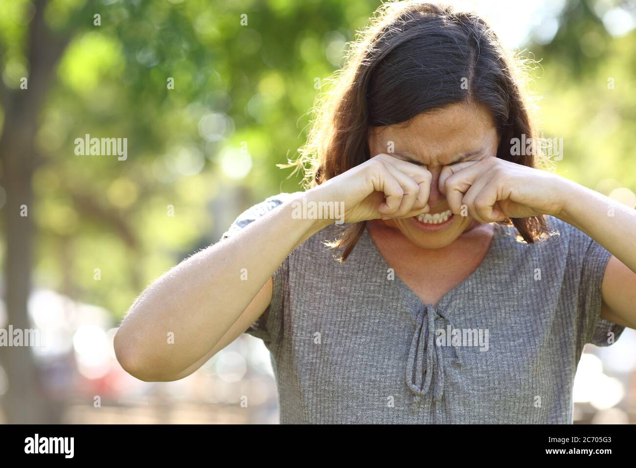 Middle age woman with itchy eyes scratching standing in the park at summer Stock Photo