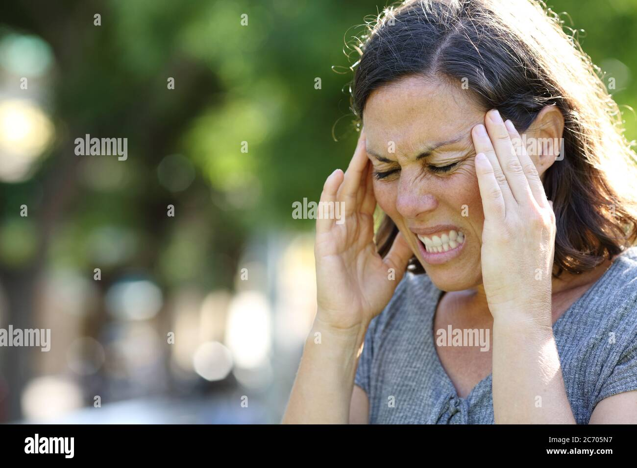 Adult woman in pain suffering migraine standing in the park at summer Stock Photo