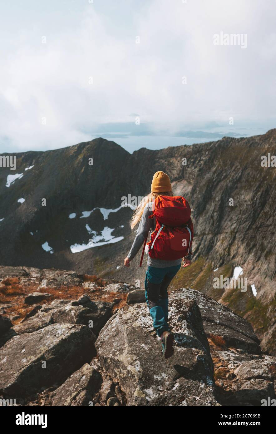 Woman trail running in mountains with red backpack travel lifestyle hiking solo active summer vacations outdoor adventure journey in Norway Stock Photo