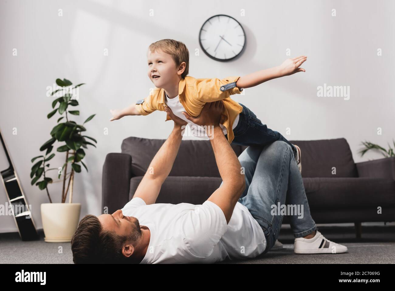 father lying in floor and holding adorabe son imitating flying with outstretched hands Stock Photo