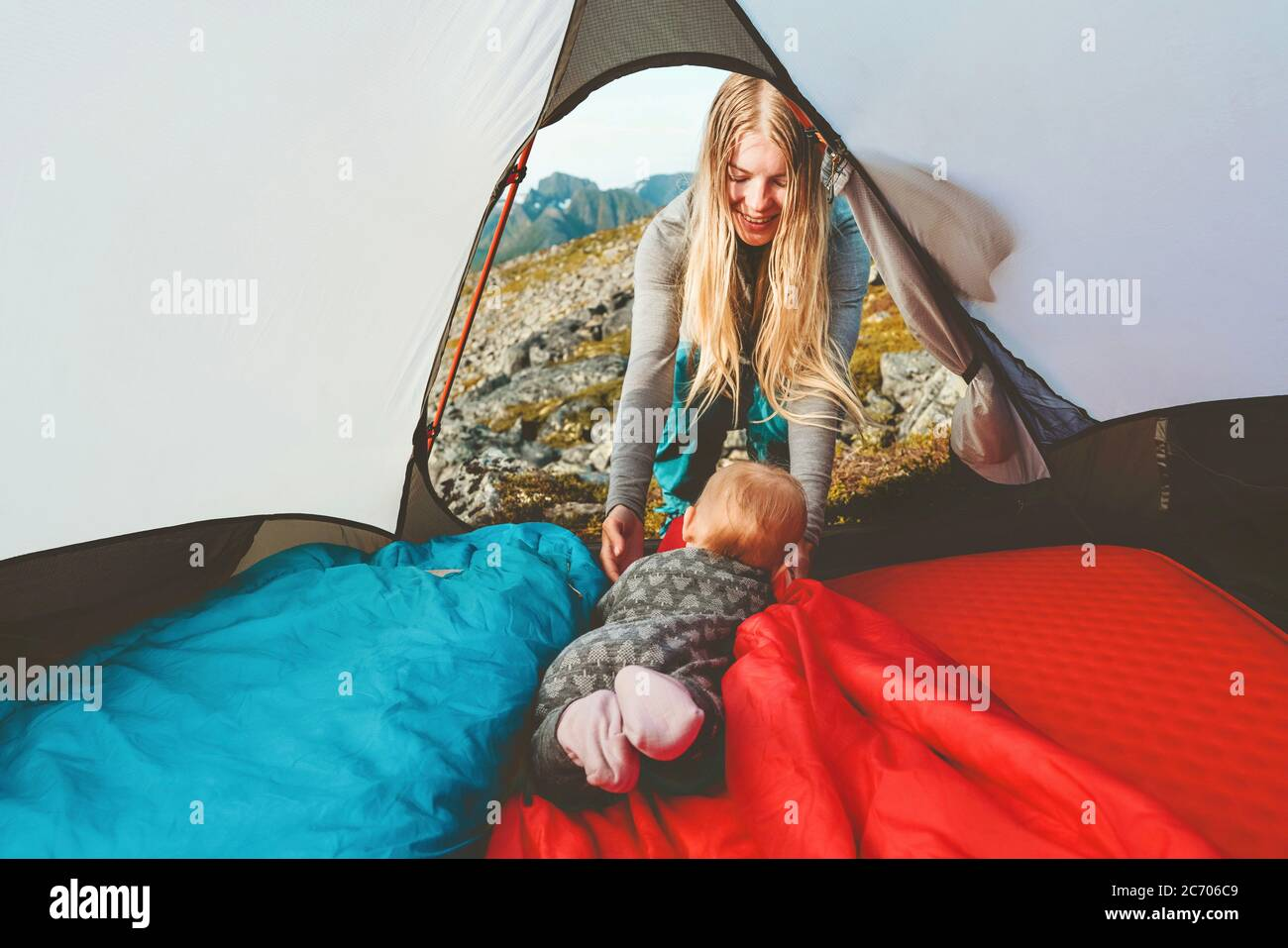 Baby and mother in camping tent family travel vacation adventure lifestyle child hiking with parents outdoor gear equipment Stock Photo