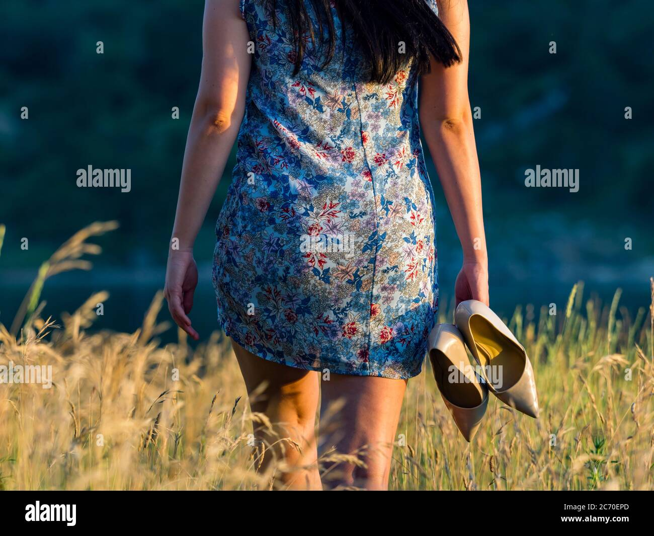 Aka young woman with high heels in hand walking going away in nature getaway runaway crop cropped view isolated bum booty Stock Photo