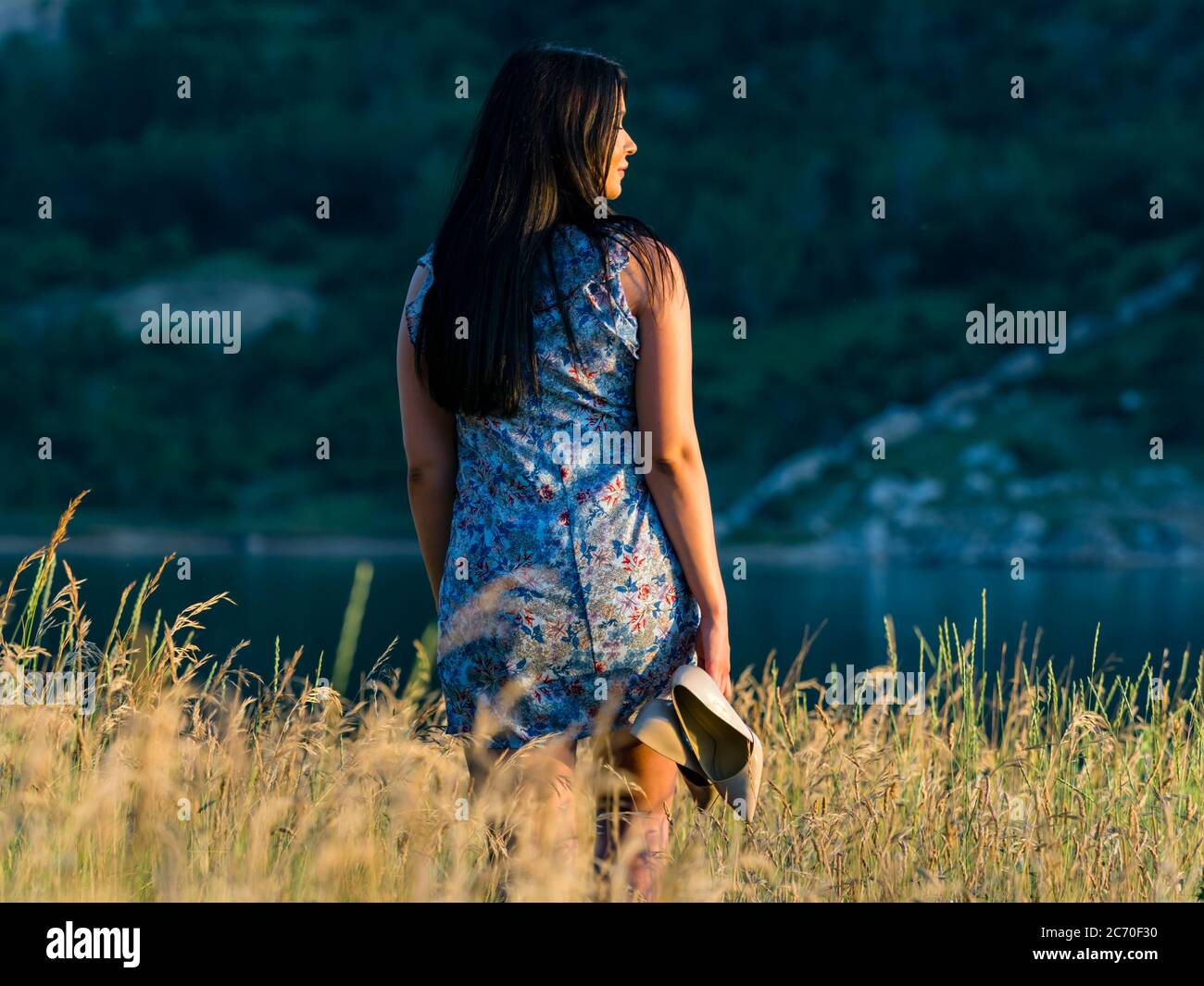 Aka young woman with high heels in hand walking going away in nature getaway runaway looking watching warm sunset in distance away aside Stock Photo
