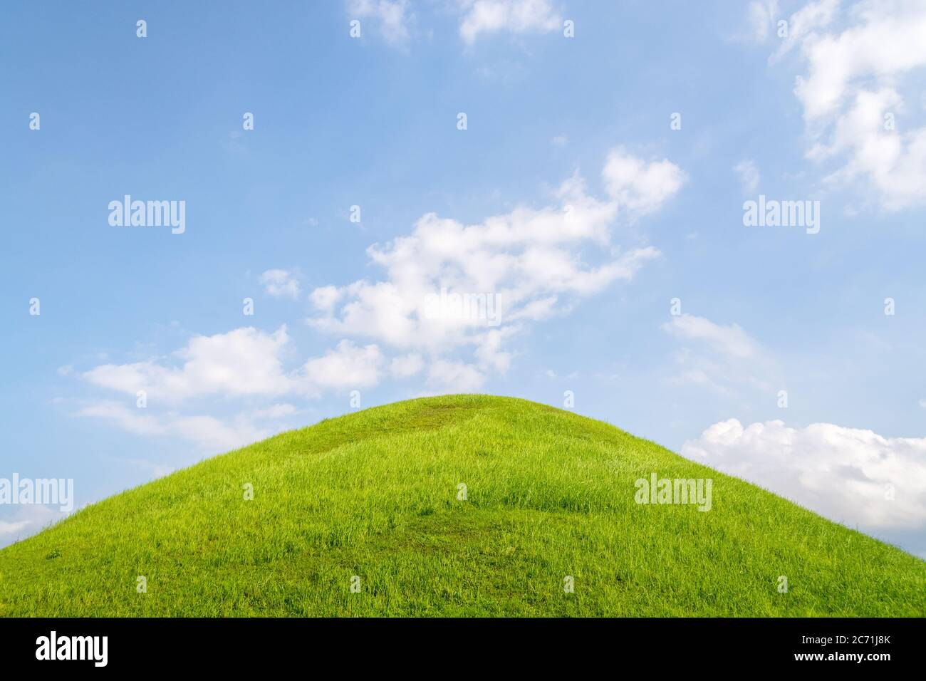 Royal tomb in Daeruengwon, Gyeongju, Korea. Capital city of Silla dynasty - Verdant hill on a sunny day with clear sky and some clouds. Stock Photo