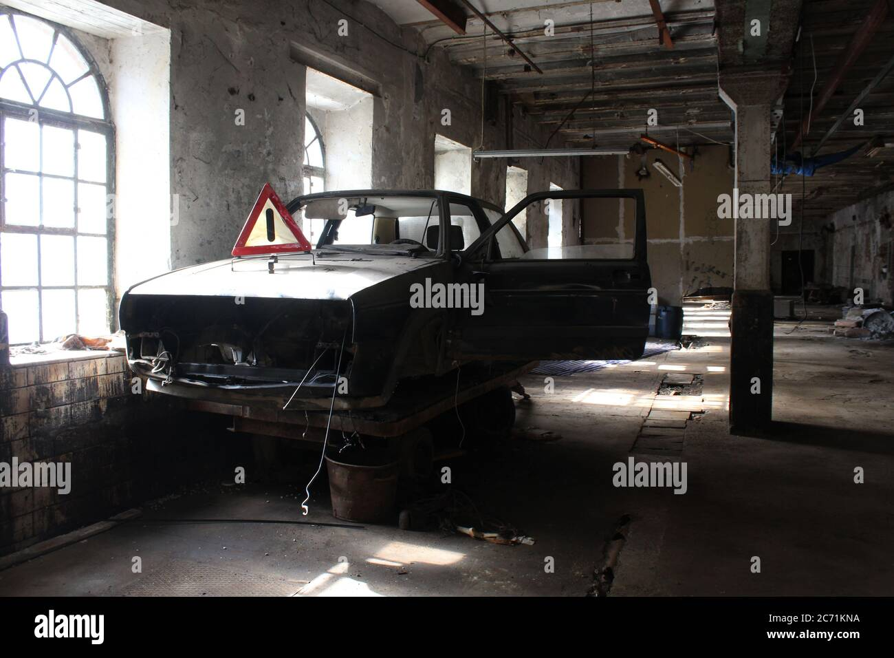 Dusty Volkswagen Golf II wreckage in an old industry facility in Altena, NRW, Germany, with a Warndreieck (warning triangle) on its engine hood. Stock Photo