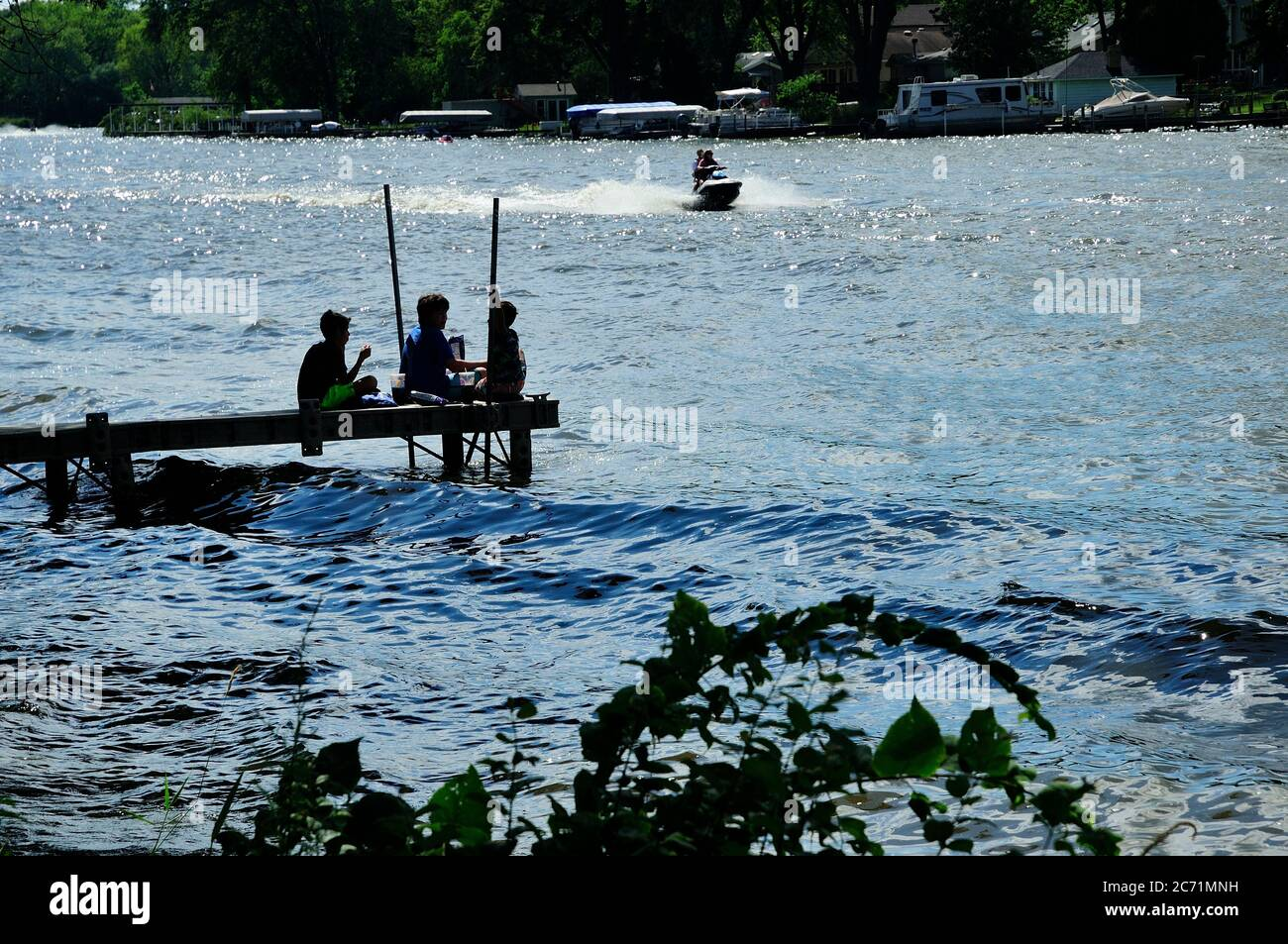 Three young boys having lunch on end of river pier. Stock Photo