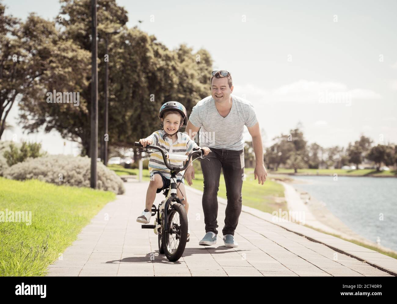 Boy learning to ride a bicycle with his father in the park by the lake. Father and son having fun together on the bikes. Happy family, outdoors activi Stock Photo