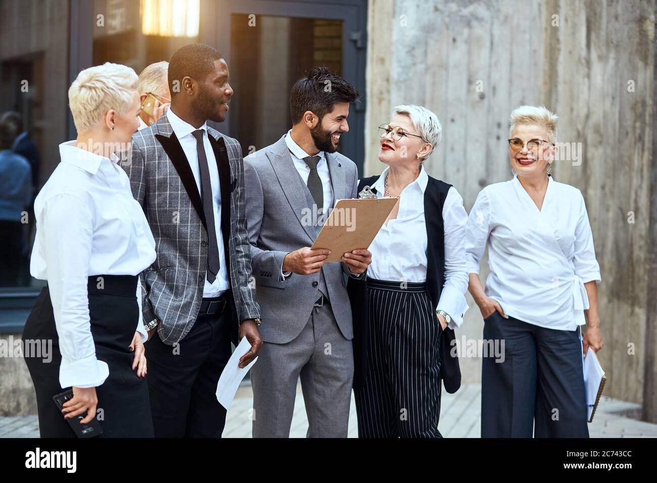 Group of businessmen move outdoor. In centre caucasian brunet bearded man in stylish grey suit smile broadly, keep papier. Woman near smile red lips, Stock Photo