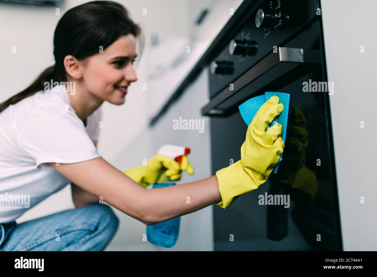 Beautiful woman in protective gloves cleaning oven with rag Stock Photo