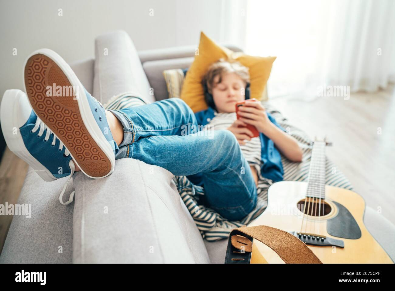 Preteen boy lying with guitar on cozy sofa dressed casual jeans and new sneakers listening to music and chatting using wireless headphones connected w Stock Photo