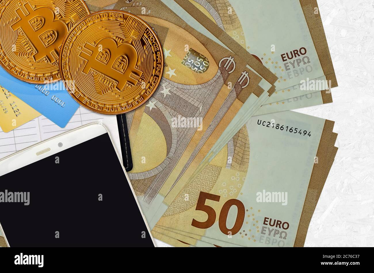 50 euro bills and golden bitcoins with smartphone and credit cards. Cryptocurrency investment concept. Crypto mining or trading transactions Stock Photo