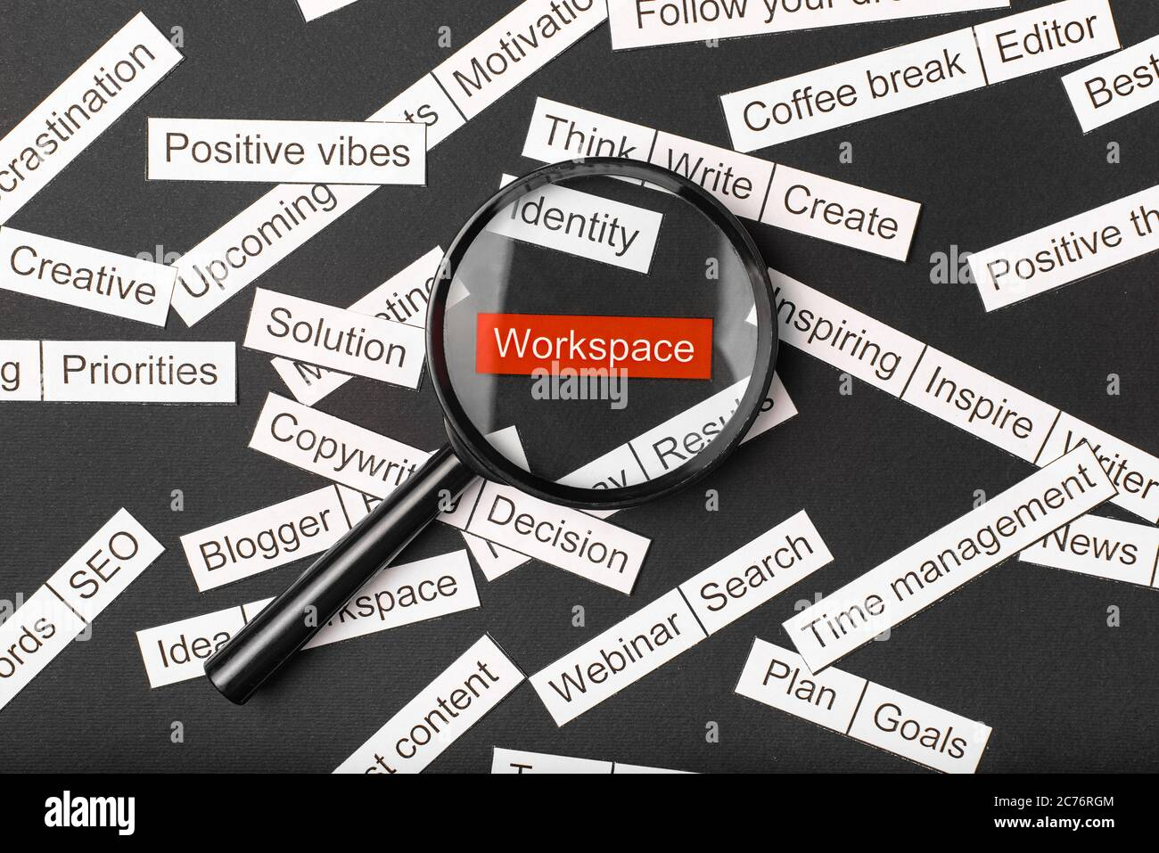 Magnifier glass over the red inscription workspace cut out of paper. Surrounded by other inscriptions on a dark background. Word cloud concept. Stock Photo
