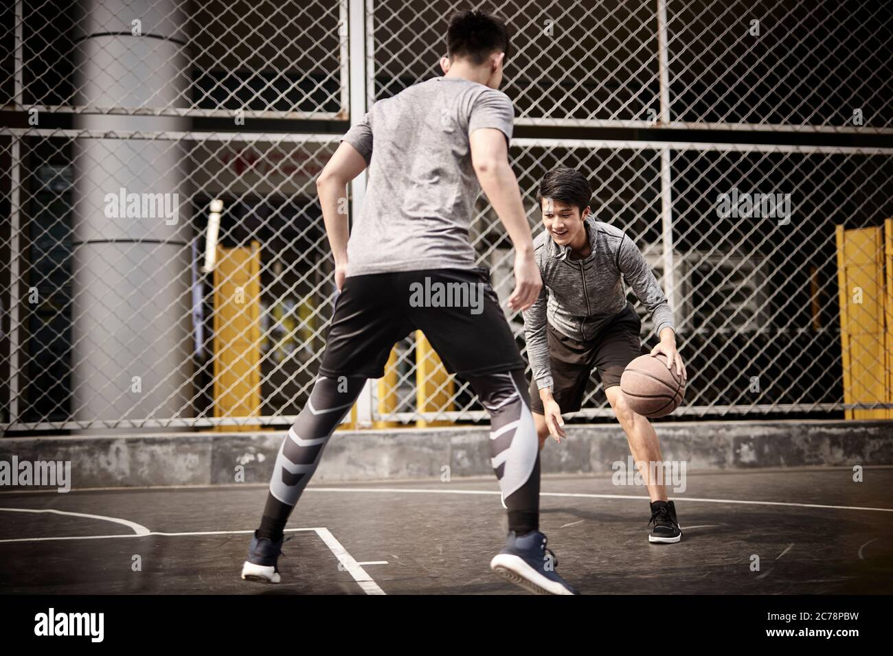 two young asian adult men playing one-on-one basketball on outdoor court Stock Photo