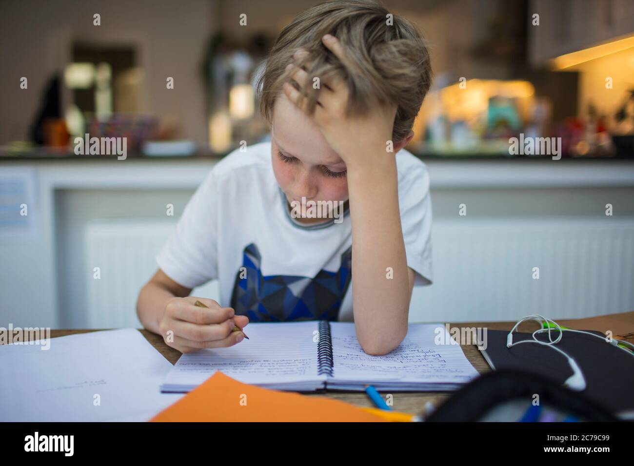 Focused boy doing homework at table Stock Photo
