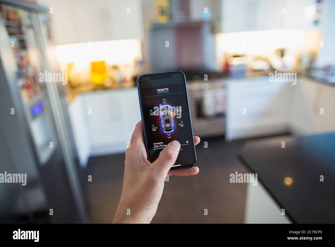 POV Man securing car alarm from smart phone screen in kitchen Stock Photo