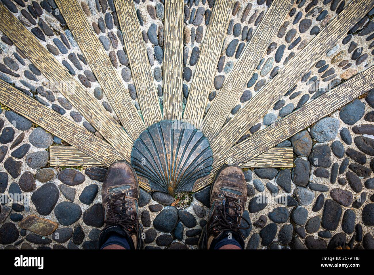 The way of saint James or compostelle . well worn Walking shoes with scallop shell.Nasbinals Lozere,France. Stock Photo